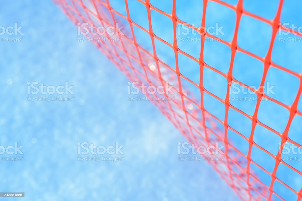 Plastic safety net for construction site. Construction mesh on winter snow background stock photo