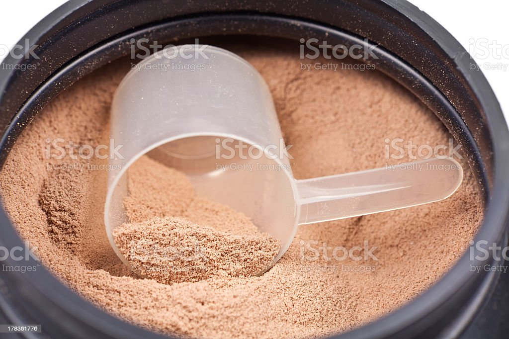 Plastic scooper inside a chocolate whey protein powder can royalty-free stock photo