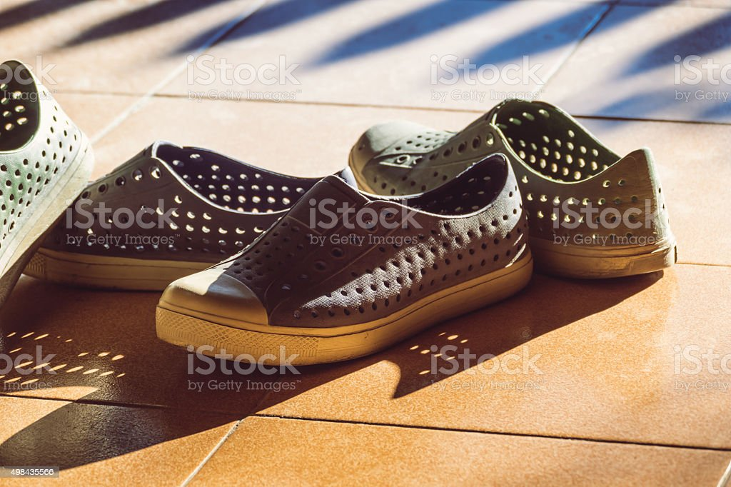 Plastic shoes on tile background with copy space stock photo