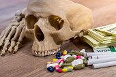 plastic skull of dollars, pills, drugs and syringes.