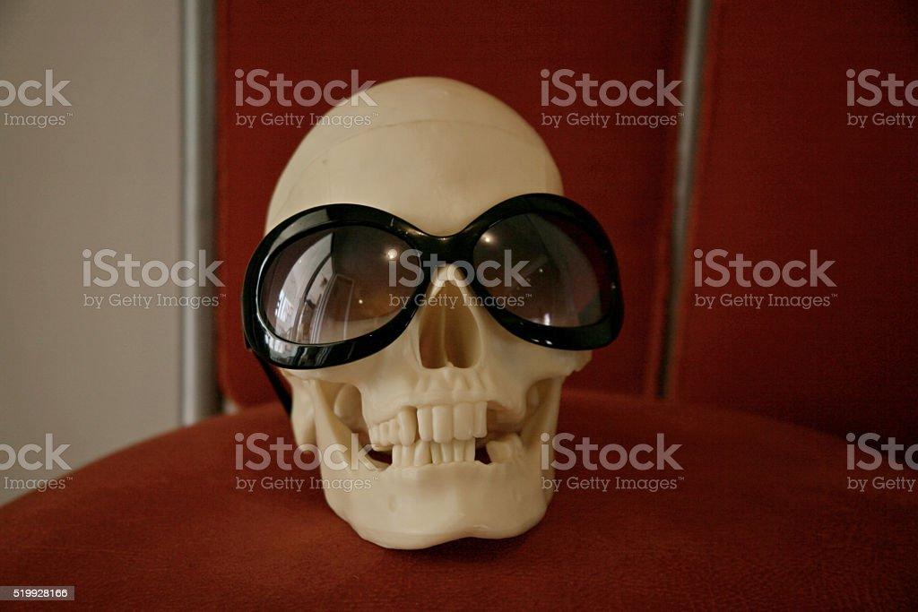 Plastic skull with sunglasses stock photo