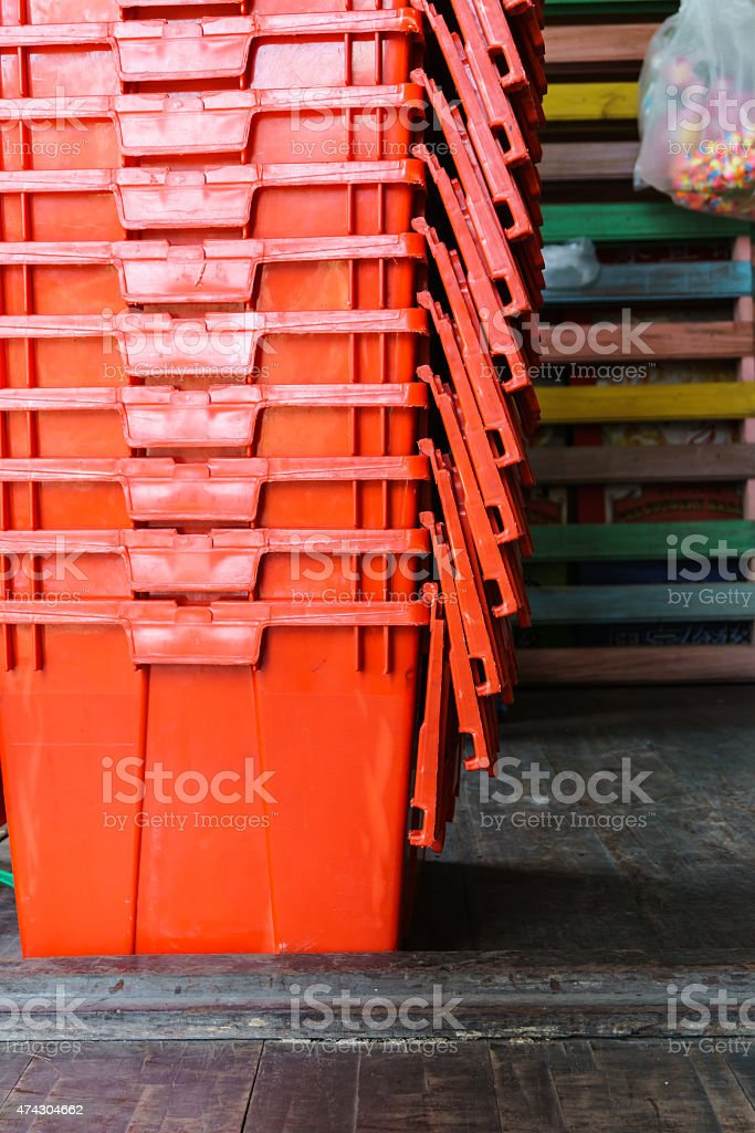 plastic storage containers stacked on wooden floor stock photo