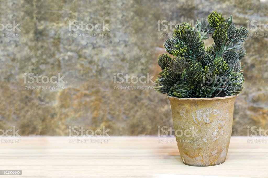 plastic tree in pot on wooden table and stone background. stock photo
