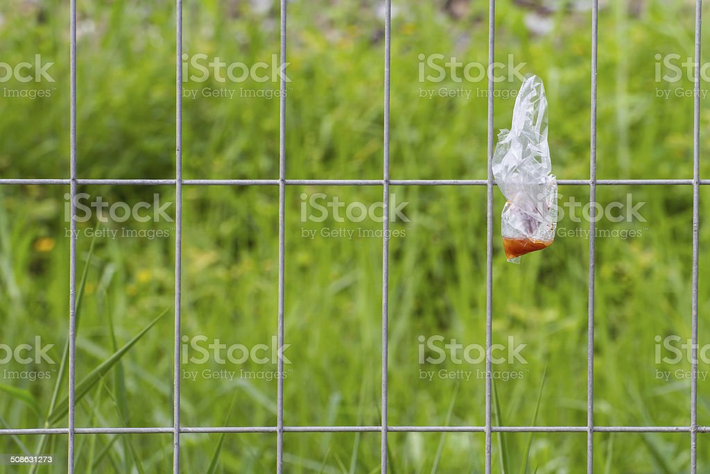 Plastic waste is disposed of irresponsibly on wire cage stock photo