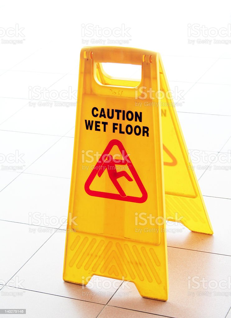 A plastic yellow barrier warning people of a wet floor stock photo