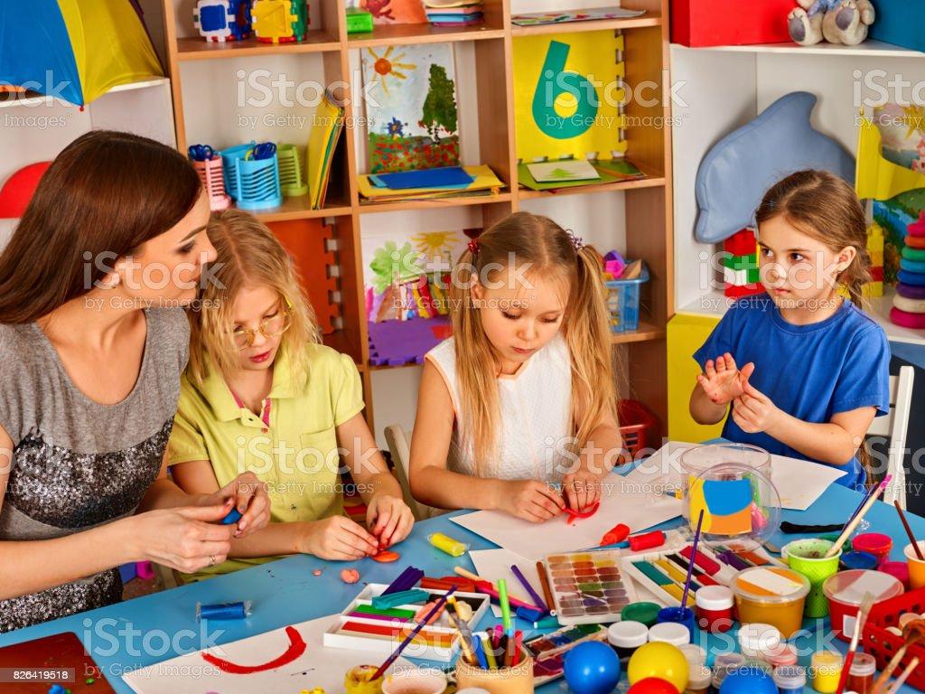 Plasticine modeling clay in children class. Teacher teaches kids...