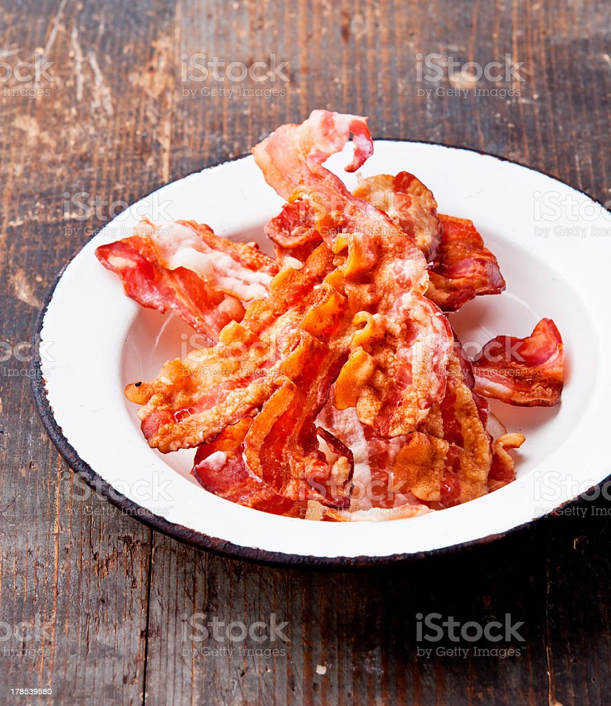 A plate filled with fried bacon on a wooden counter stock photo