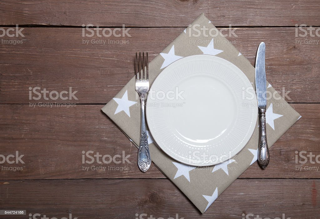 Plate, fork and knife on napkin on wooden background stock photo