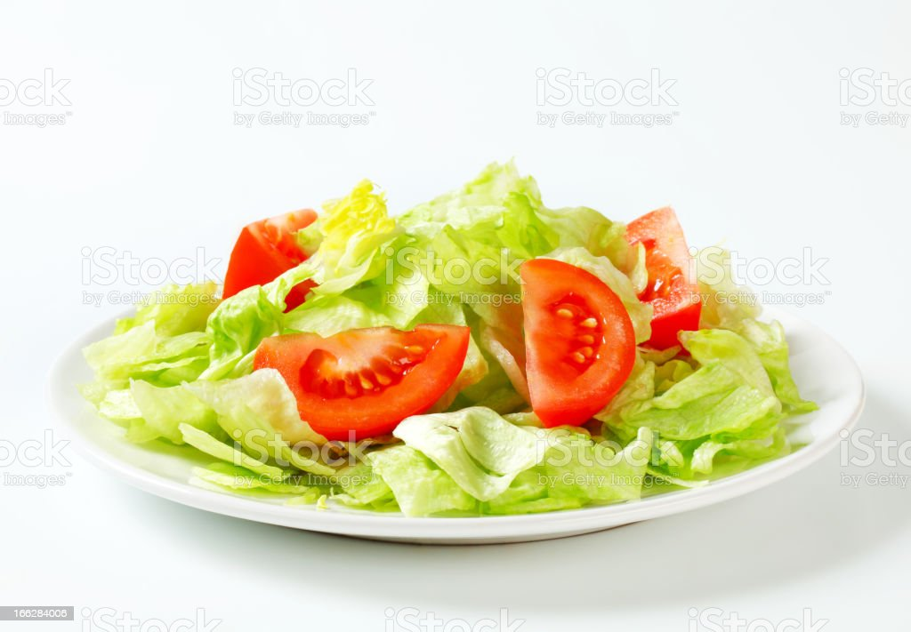 Plate full of cut up iceberg lettuce and tomato wedges stock photo