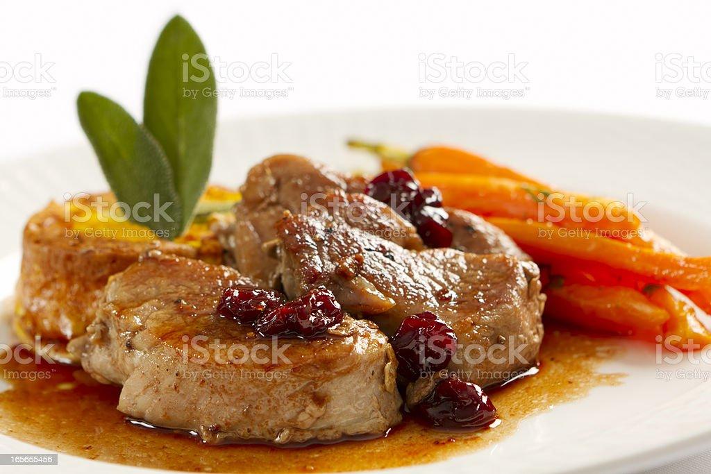 Plate full of pork loin medallions and carrots stock photo