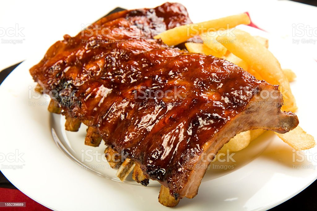 A plate of barbecue ribs and french fries stock photo