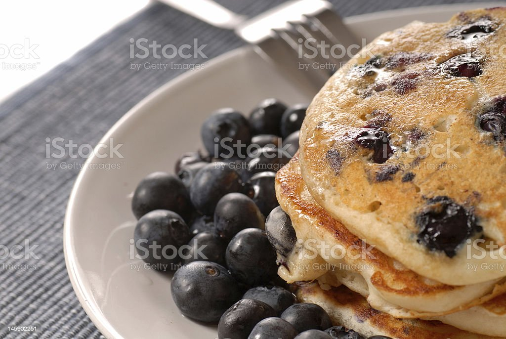 Plate of blueberry pancakes with fresh blueberries on side stock photo
