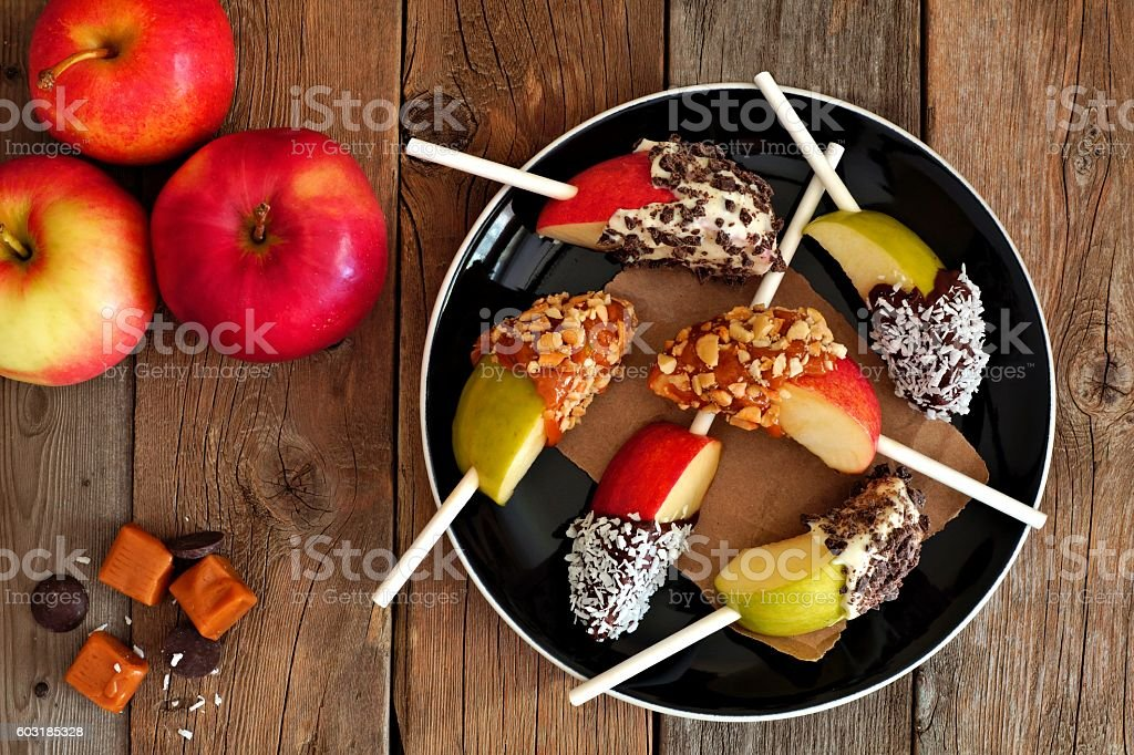 Plate of caramel and chocolate dipped apple slices, overhead scene stock photo