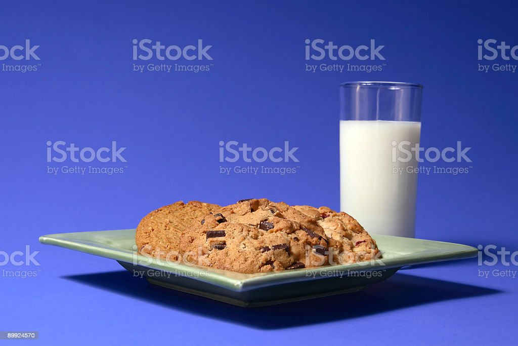 Plate of Chocolate Chip Cookies on Blue with Milk royalty-free stock photo