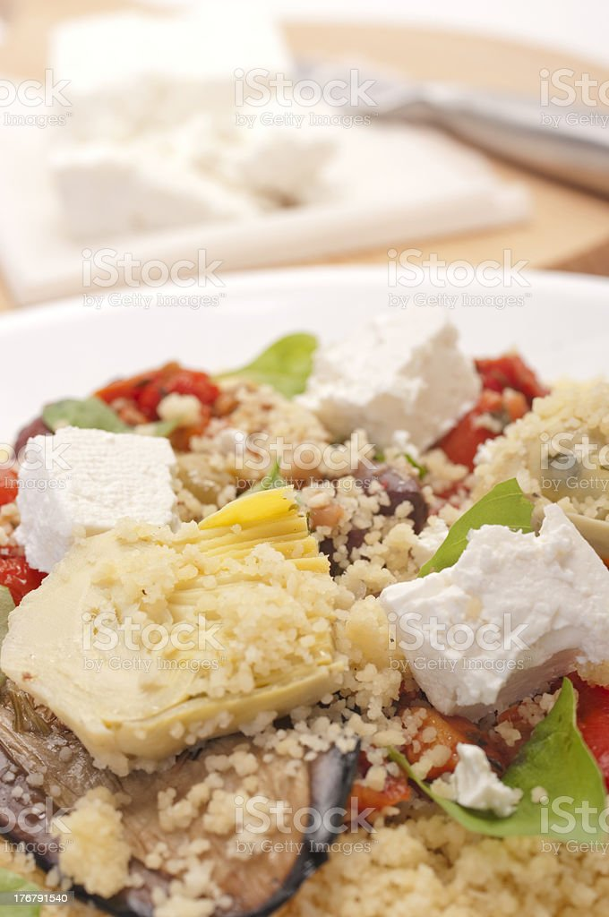 Plate of couscous with antipasto vegetables, and cheese cutting board. royalty-free stock photo