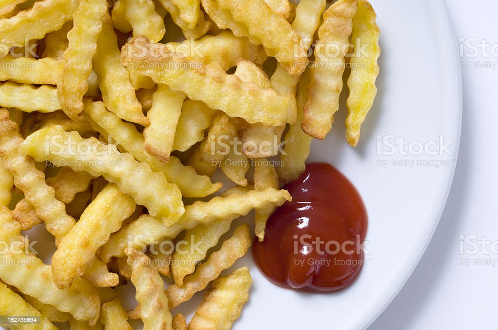 Plate Of Crinkle Cut Chips or Fries Ketchup White Background royalty-free stock photo