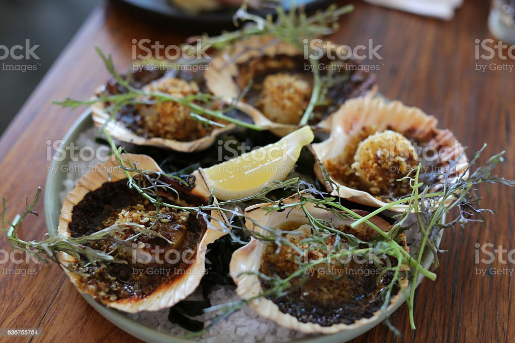 Plate of crumbed scallops in clam shells, seafood restaurant stock photo