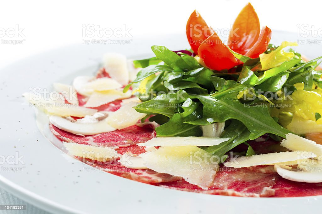 Plate of delicious beef carpaccio with salad and cheese stock photo