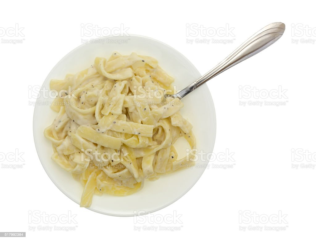 Plate of fettuccine alfredo with fork on white background stock photo