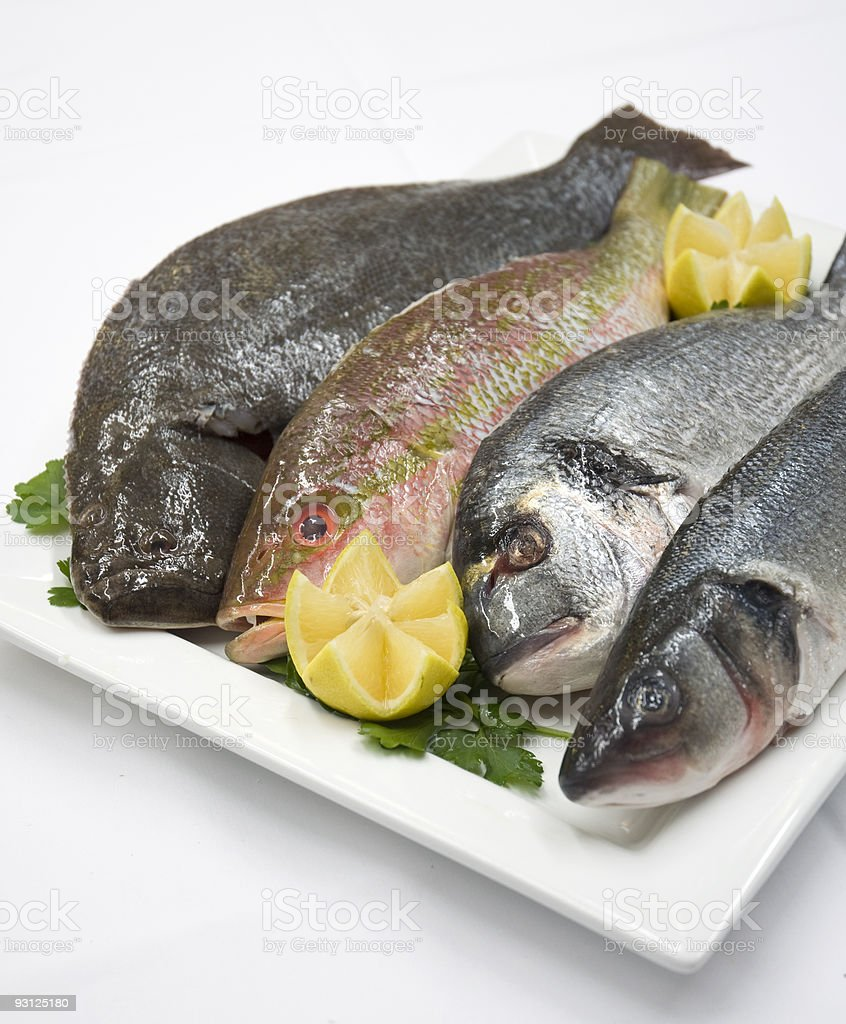 Plate Of Fresh Fish With Lemon Garnish stock photo