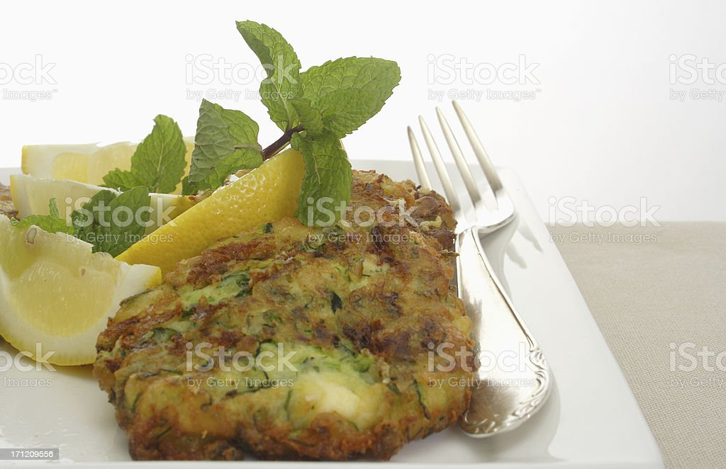 plate of fresh zuchini fritters with fork stock photo
