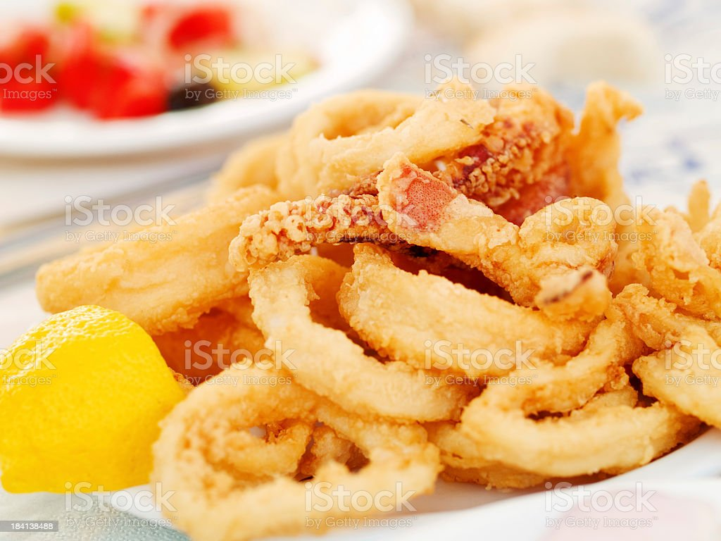 A plate of fried calamari with half a lemon by the side royalty-free stock photo
