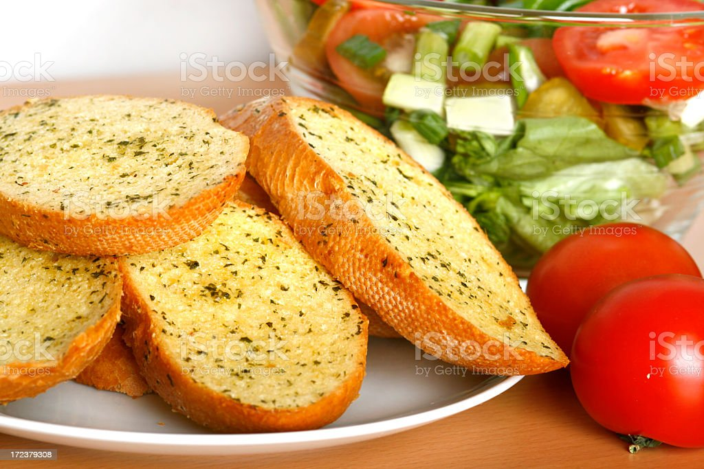 A plate of garlic bread with tomatoes and salad on a table stock photo