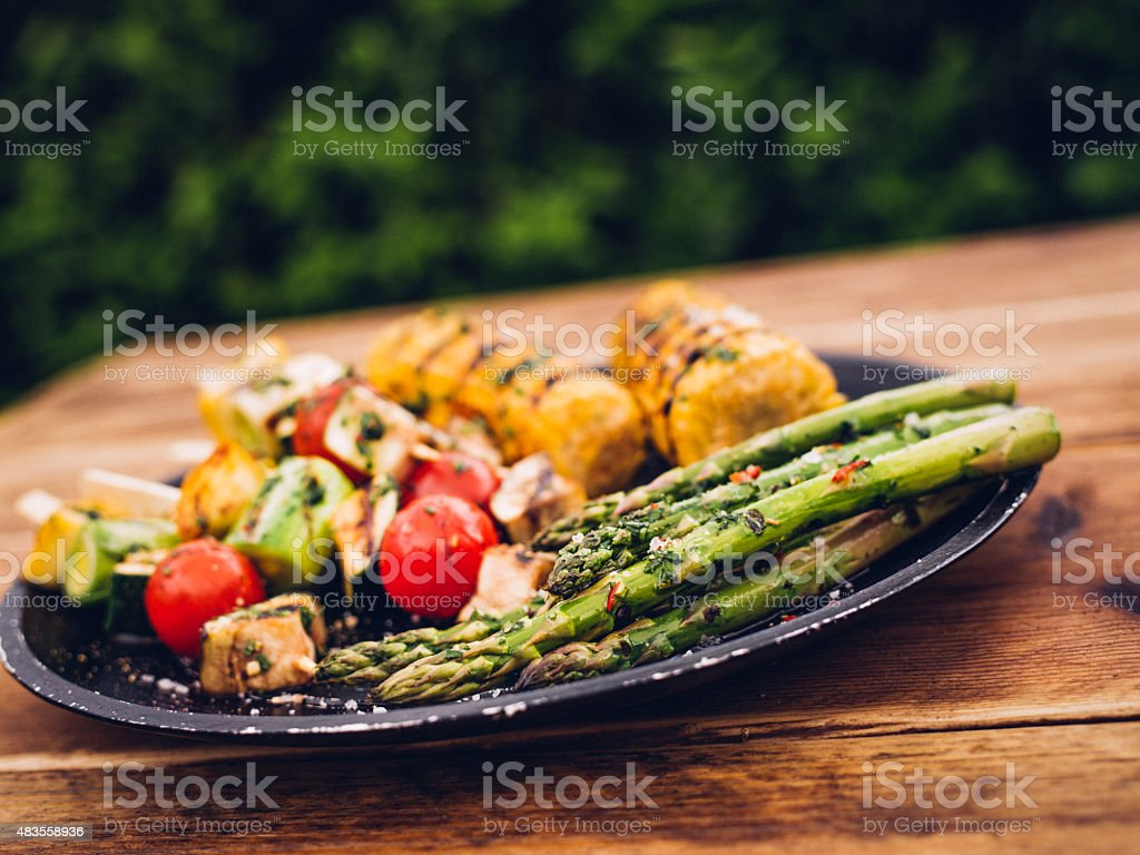 Plate of grilled vegetables on a wooden table outdoors stock photo