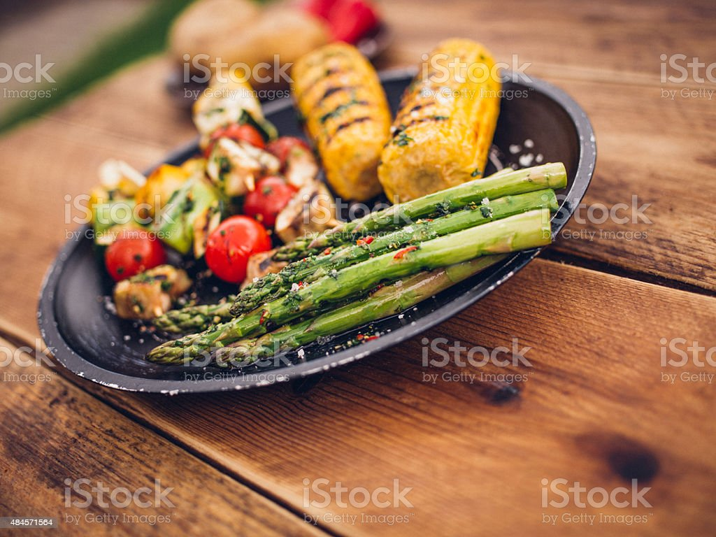 Plate of healthy grilled vegetables on a wooden table outdoors stock photo