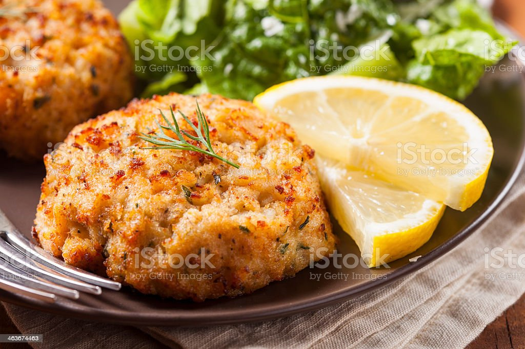 Plate of homemade organic crab cakes with veg and lemon stock photo