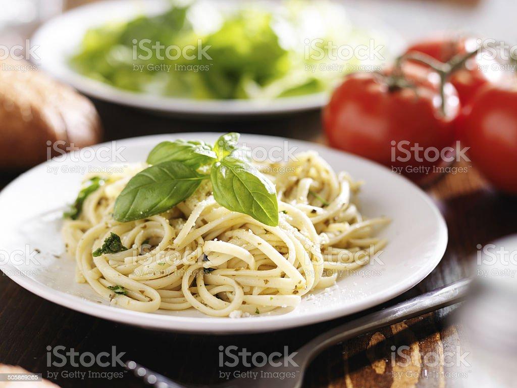 plate of italian spaghetti with pesto sauce stock photo