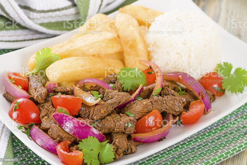 Plate of Lomo Saltado on a white plate in a green towel stock photo