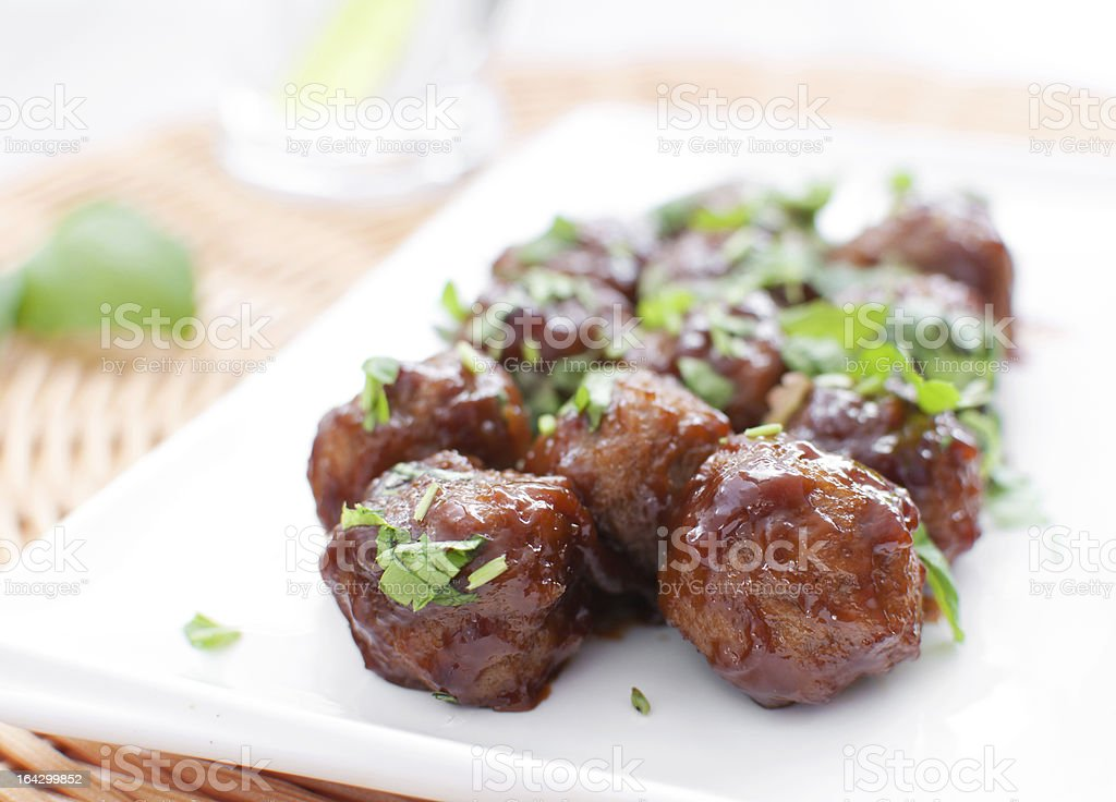 Plate of meatballs in gravy with herbs stock photo