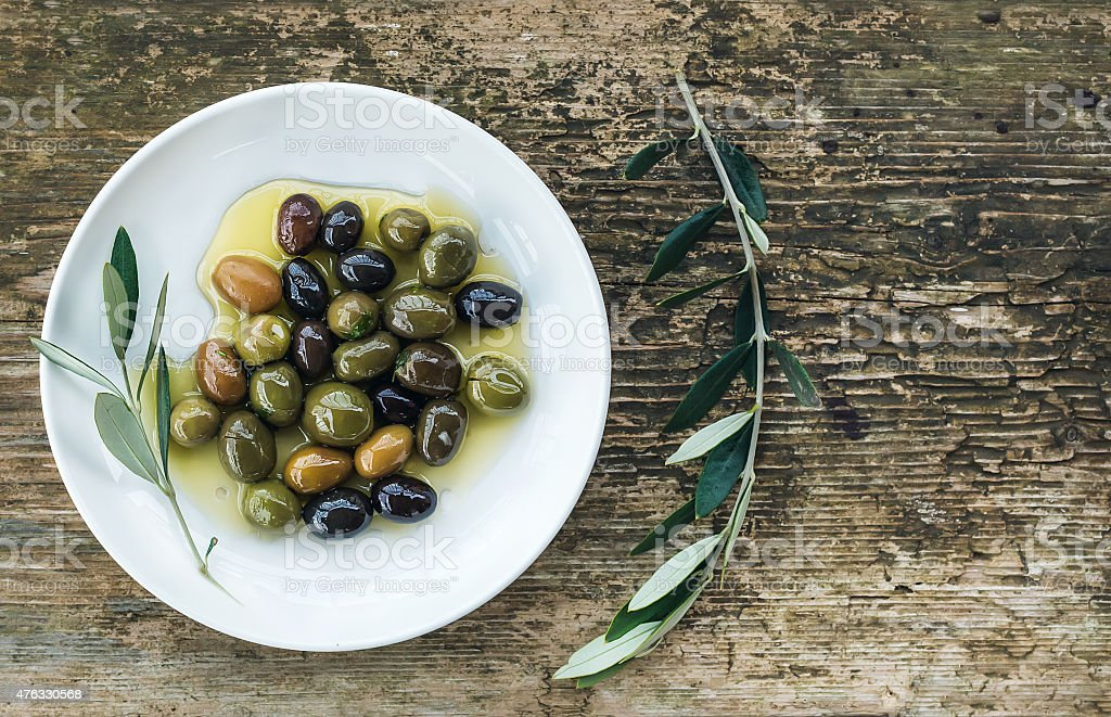 Plate of Mediterranean olives in oil with tree branch stock photo