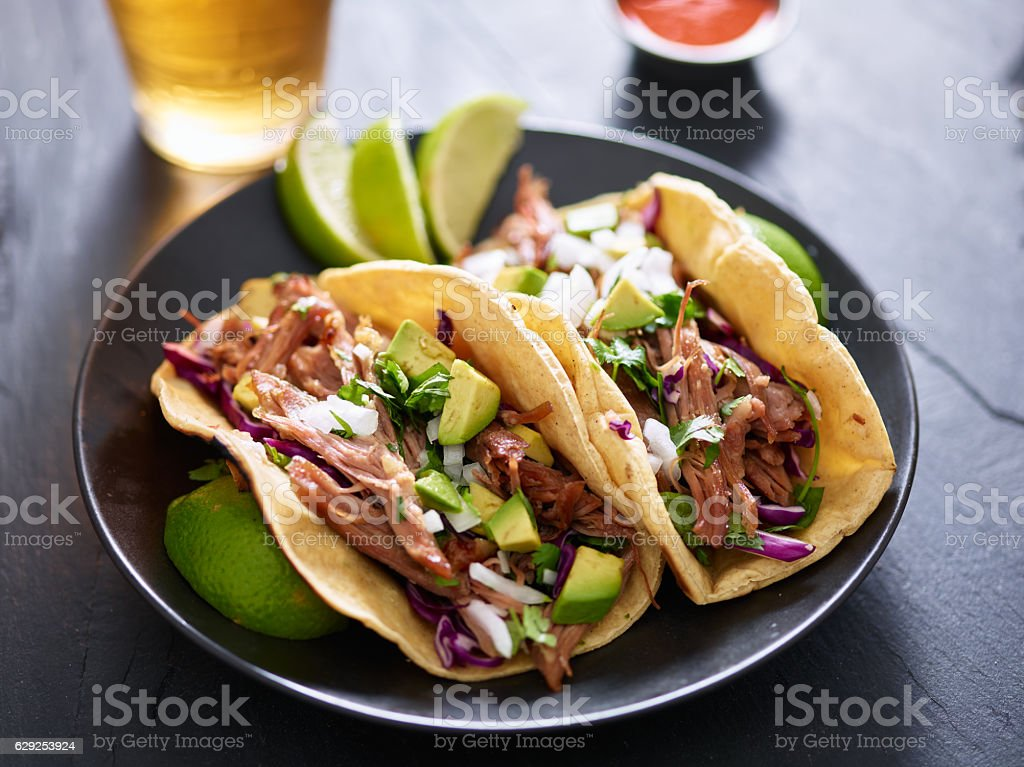 plate of mexican carnita tacos with beer in background stock photo