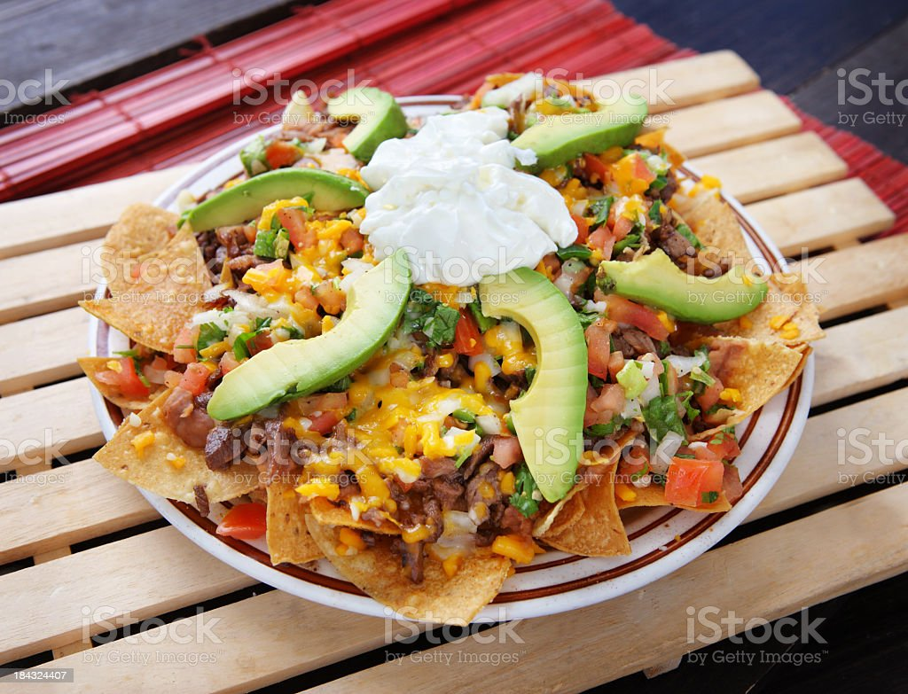 Plate of nachos with avocado, cheese and vegetables stock photo