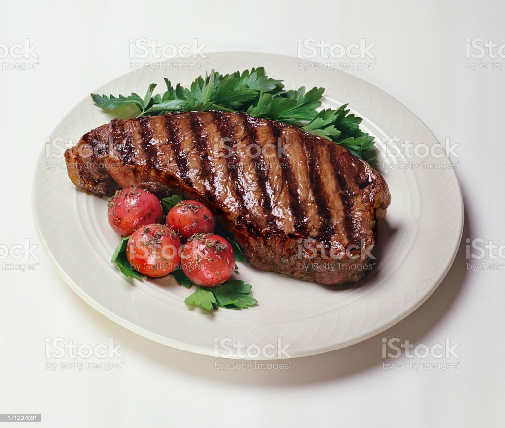 Plate of New York strip steaks with tomatoes on side stock photo