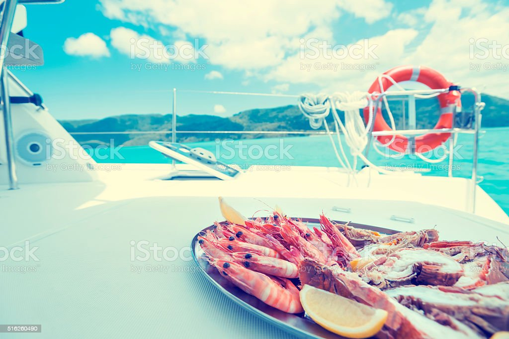 Plate of prawns and seafood being served on a boat stock photo
