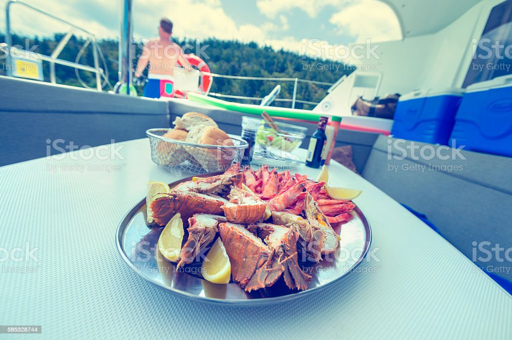 Plate of prawns and seafood being served on a boat. stock photo