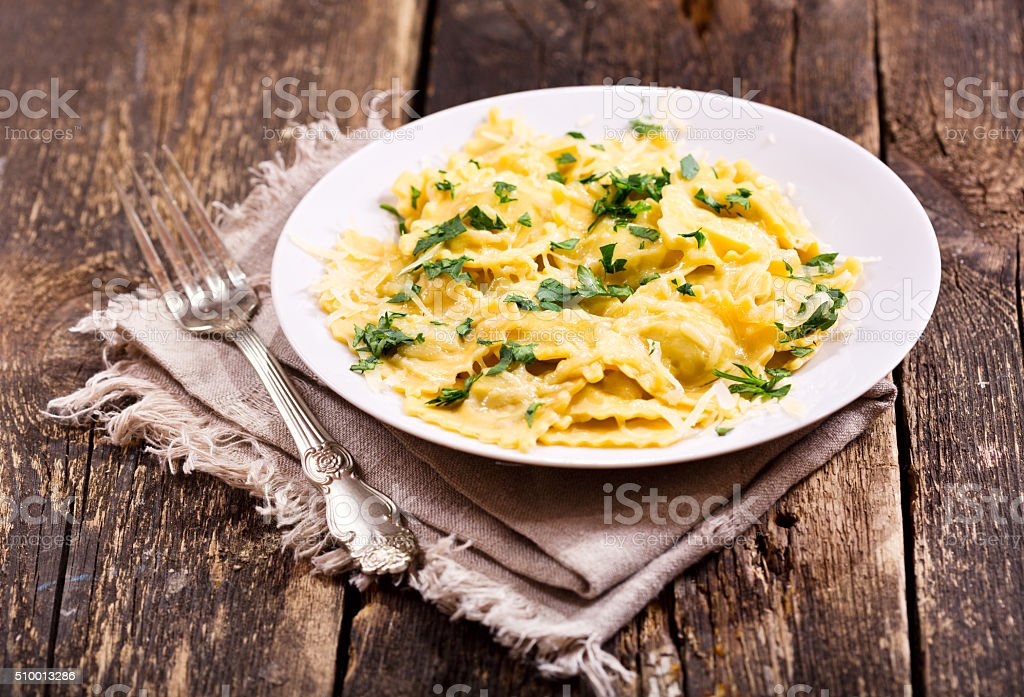 plate of ravioli on wooden table stock photo