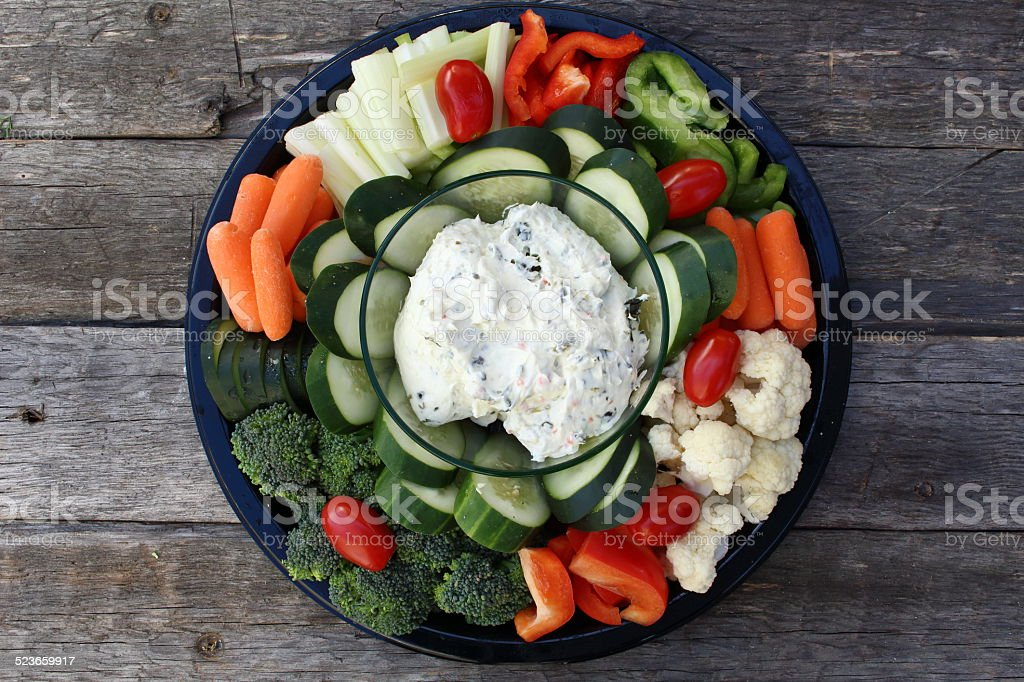 Plate of raw vegetables and dip on old wooden planks stock photo