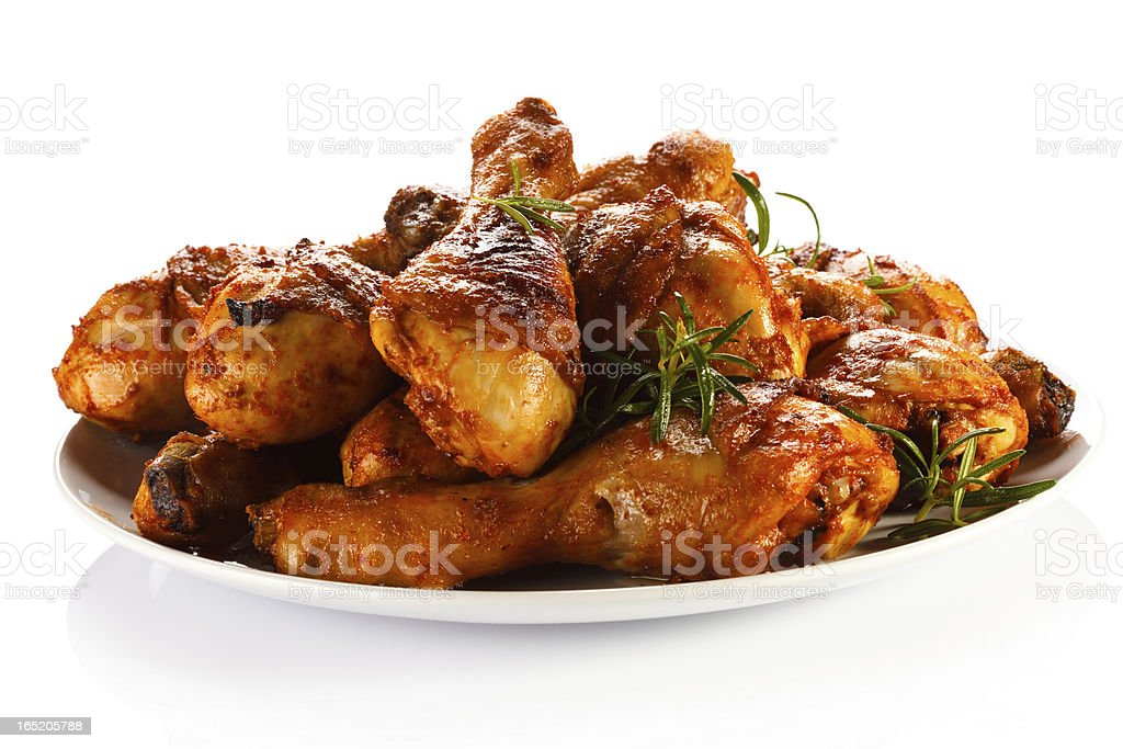 A plate of roasted chicken drumsticks stock photo