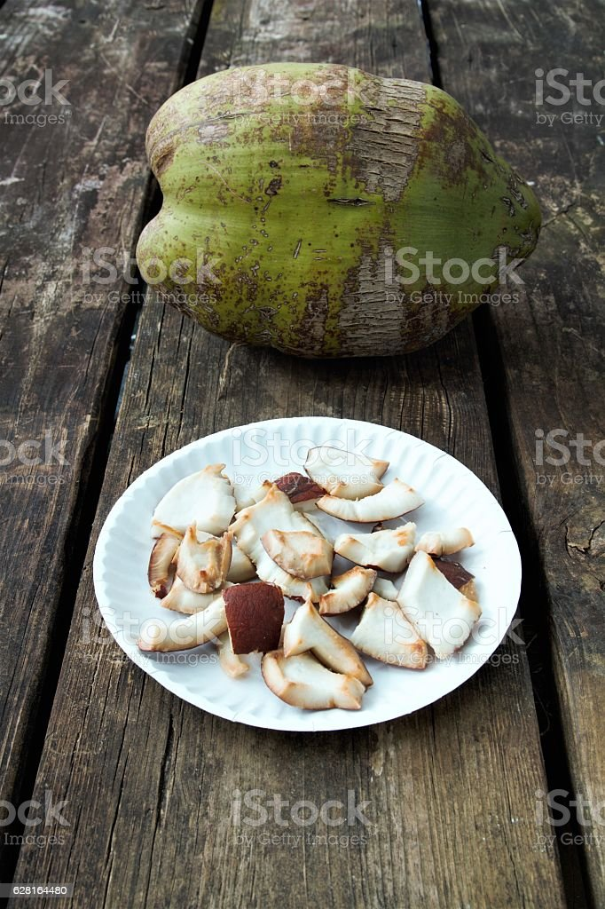 Plate of roasted coconut chunks on table with coconut stock photo