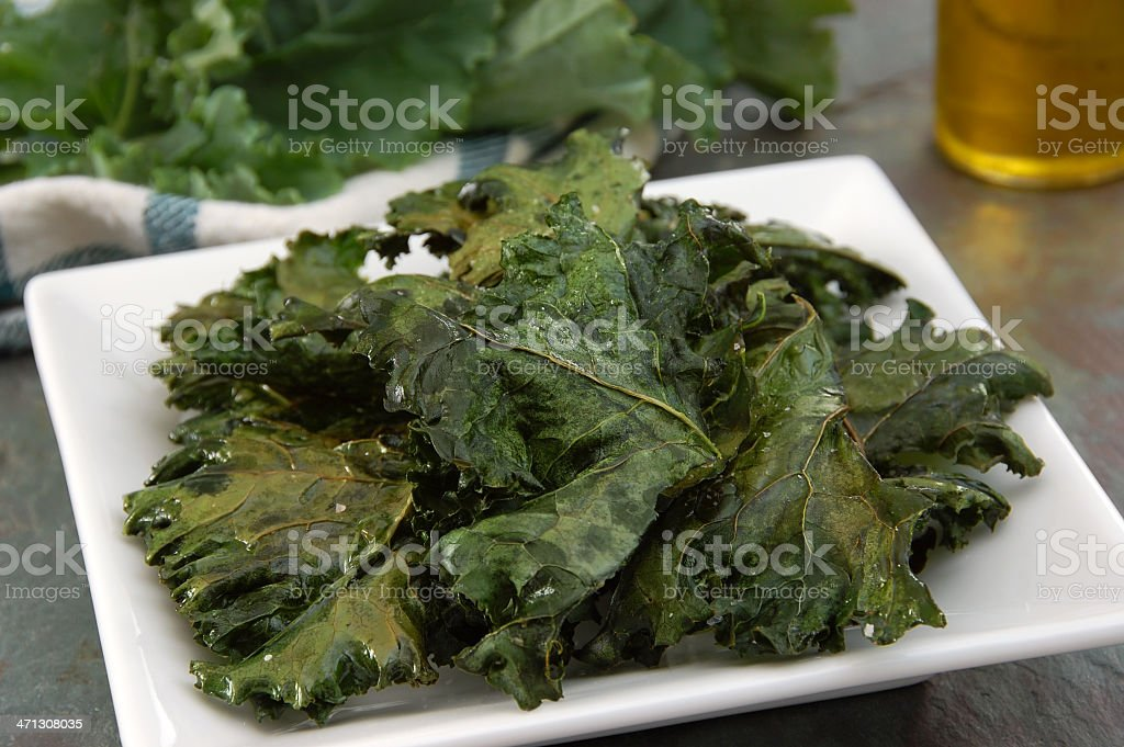A plate of salted and baked kale chips stock photo