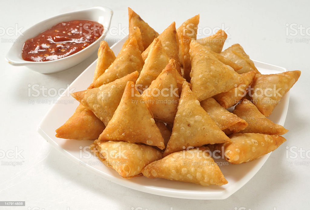 A plate of samosas and dipping sauce stock photo