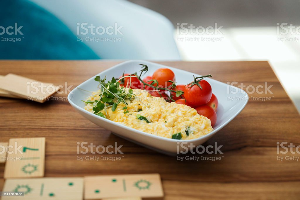 Plate of scrambled eggs with cherry tomatos and wooden dominos. stock photo