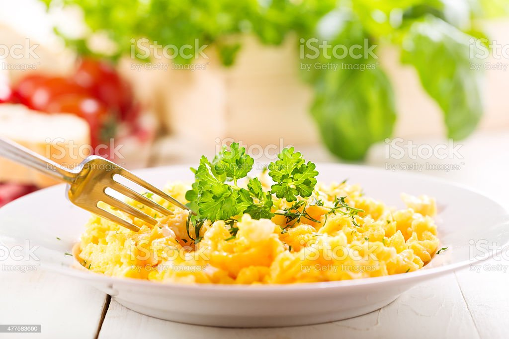 plate of scrambled eggs with parsley stock photo