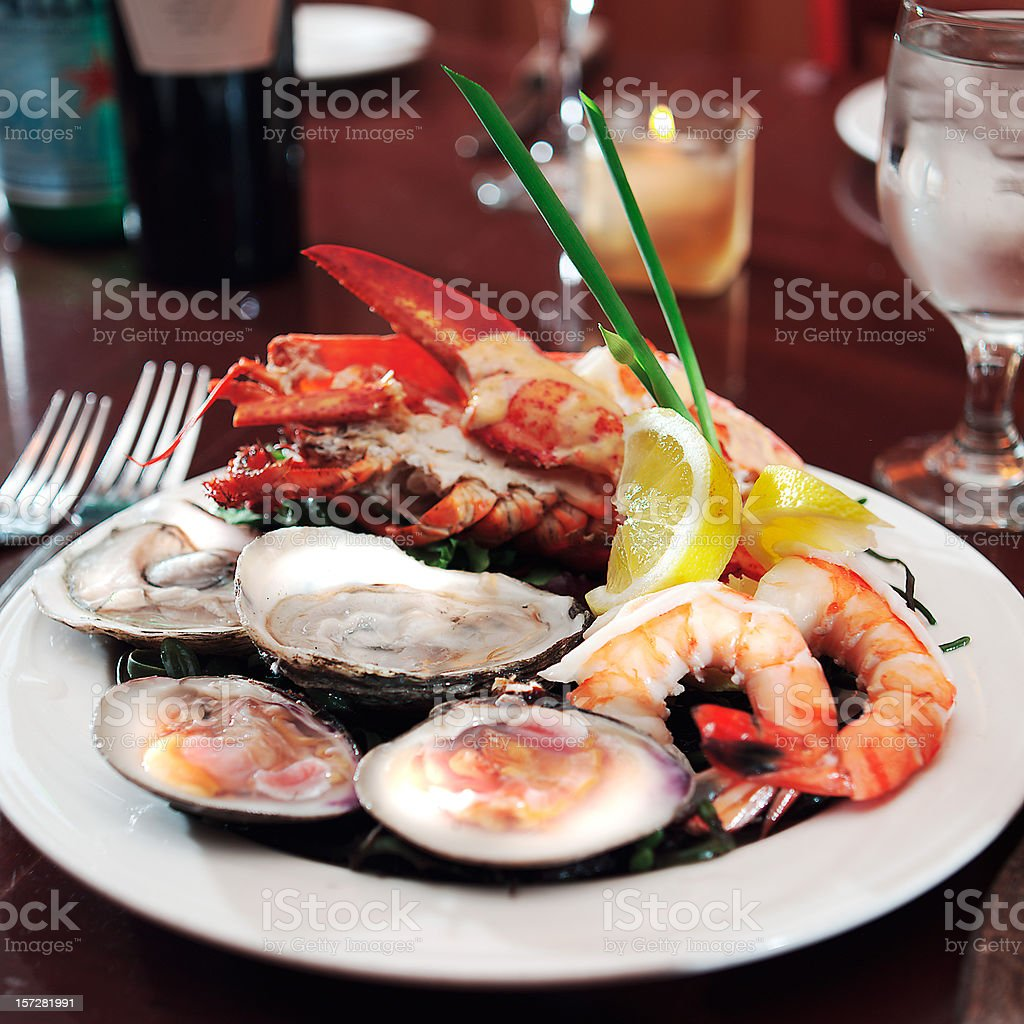 Plate of seafood on table with fork and glass stock photo