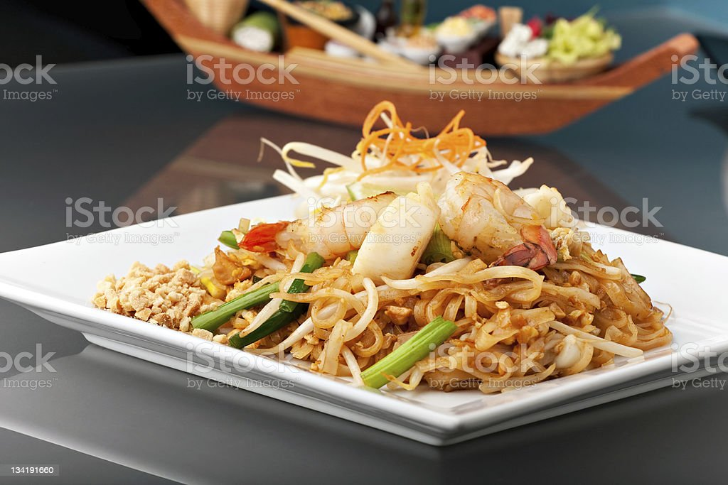 A plate of seafood pad Thai with stir fried rice noodles stock photo