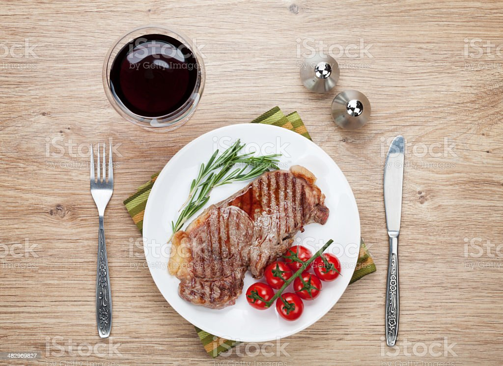 Plate of sirloin steak with tomatoes and rosemary stock photo